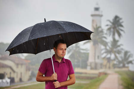 Man with black umbrella in heavy rain photo