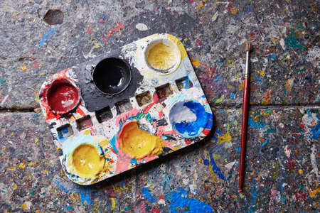 workbench: Palette with paintbrush on the desk in workshop