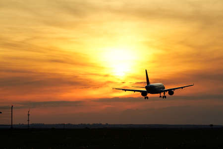 airplane landing: Airplane is landing at the sunset.  Stock Photo
