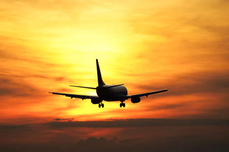 airplane take off: Airplane is landing at the sunset.  Stock Photo
