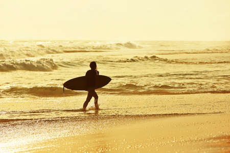 adventure holiday: Woman with surfboard on the beach at sunset. Stock Photo