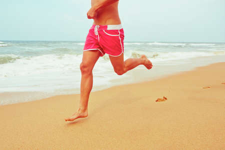 bare foot: Young man is running on the beach