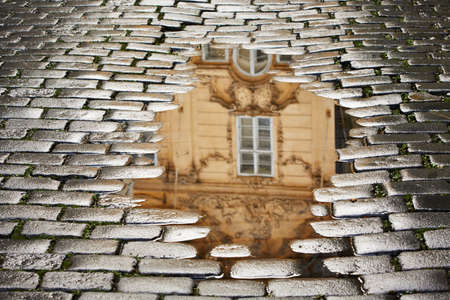 After rain in Prague - reflection of the house in puddle Stock Photo