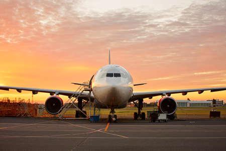 Het onderhoud van vliegtuigen - grote vliegtuigen op de prachtige zonsopgang