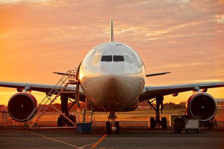 航空機サービス - 美しい日の出に大型航空機