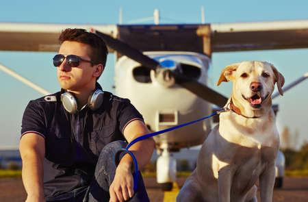 犬を持つ若い操縦者が飛行機の前に座っています。