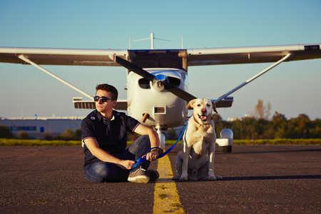 犬を持つ若いパイロットは、飛行機の前に座っています。