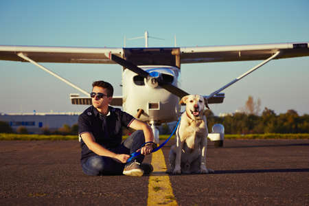 pilotos aviadores: Piloto joven con el perro est� sentado en frente del avi�n Foto de archivo