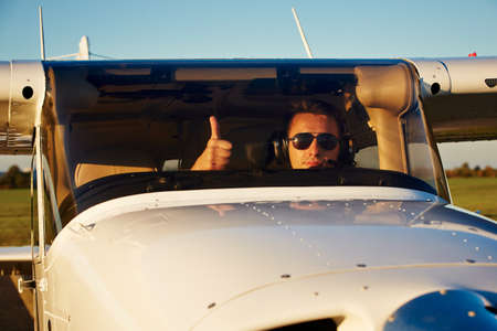 Young pilot is preparing for take off with private plane. Stock Photo