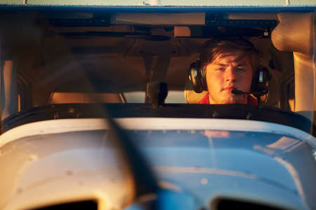 Young pilot is preparing for take off with private plane. photo