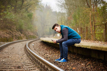 loner: Young man is waiting on the platform rural railway station Stock Photo