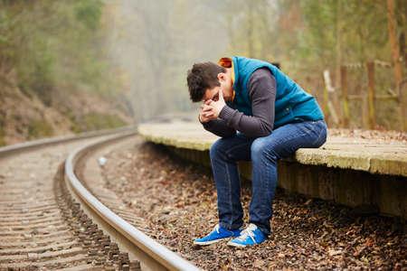 Sad young man at the railway station Foto de archivo