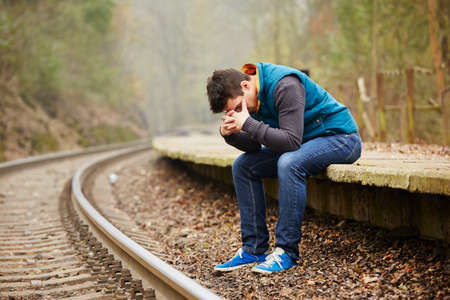 man crying: Sad young man at the railway station Stock Photo