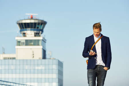 Handsome Geschäftsmann ist auf dem Flughafen warten
