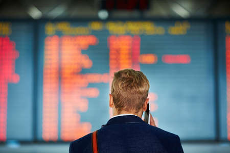 delay: Young businessman is waiting at the airport Stock Photo