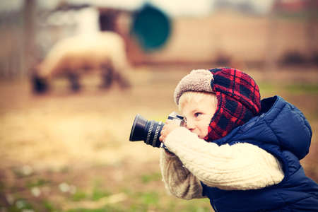 photo shooting: Little boy with camera is shooting in the farm