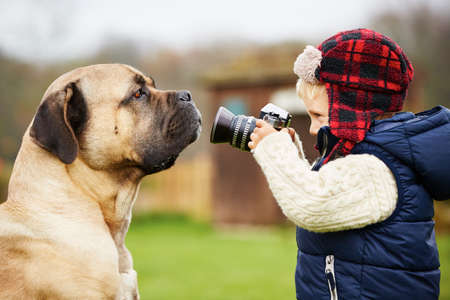 Little boy with camera is shooting his dog Stockfoto
