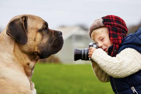 Kleiner Junge mit Kamera Dreharbeiten zu seinem Hund Standard-Bild - 33723255