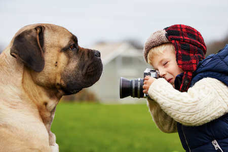 photo shooting: Little boy with camera is shooting his dog Stock Photo