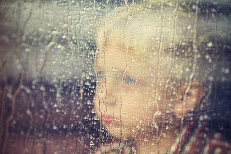 cara triste: El niño pequeño detrás de la ventana en la lluvia - enfoque selectivo