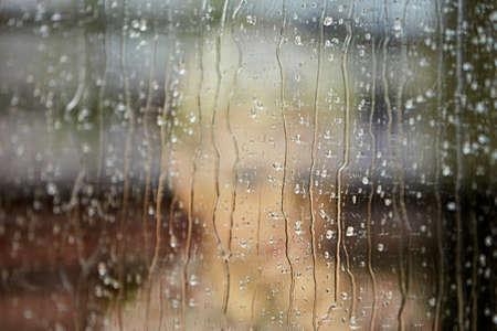 persona triste: El ni�o peque�o detr�s de la ventana en la lluvia - enfoque selectivo
