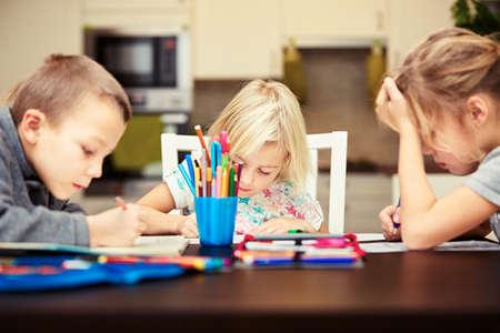 problemas familiares: Los hermanos est�n haciendo su tarea para la escuela primaria. Foto de archivo