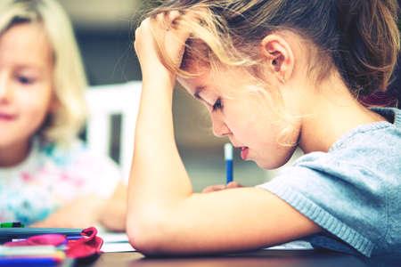 Dzieci: Rodzeństwo robią swoje zadanie domowe dla szkoły podstawowej.