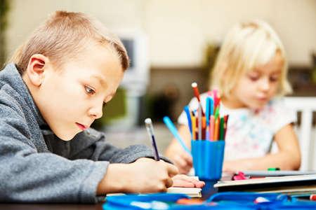 niños pintando: Los hermanos están haciendo su tarea para la escuela primaria. Foto de archivo