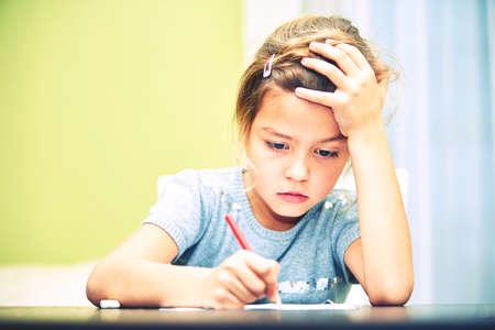Kleines Mädchen macht seine Hausaufgaben für die Grundschule.