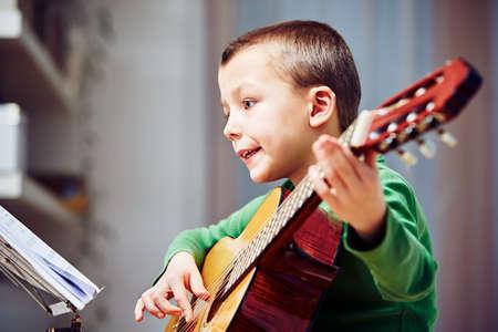 niño cantando: El niño pequeño está tocando la guitarra en su casa