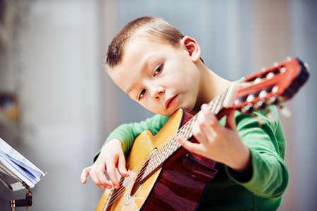 kinderen: Kleine jongen speelt de gitaar thuis