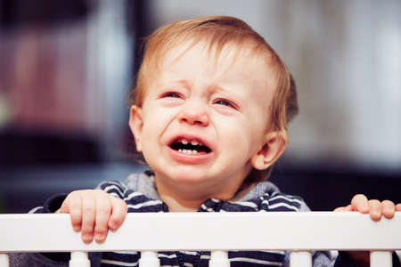 baby crying: Little boy is crying in the bed Stock Photo