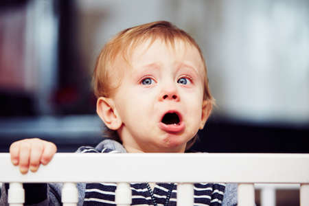 小さな男の子がベッドで泣いています。
