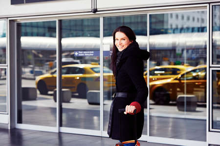 Successful woman in front of the terminal at the airport.