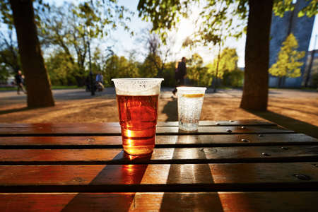 sun light: Cups of beer and water in the garden restaurant Stock Photo