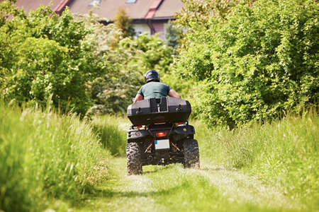 Man in helmet is driving the all terrain vehicle in nature near city.