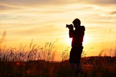 夕暮れ時、若いカメラマンのシルエット。