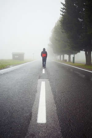 distance: Lonely man is walking in mysterious fog
