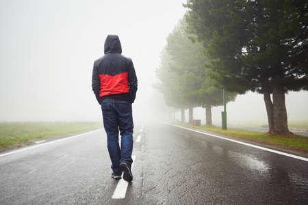 fila de personas: Hombre solo es caminar en la niebla misteriosa Foto de archivo