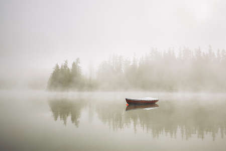朝の霧の湖にボートします。