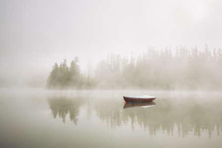 silencio: Barco en el lago en niebla de la mañana. Foto de archivo