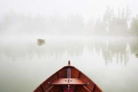 朝の霧の湖ではボート。 写真素材