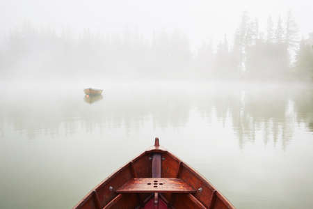 fishing lake: Boats on the lake at morning fog.