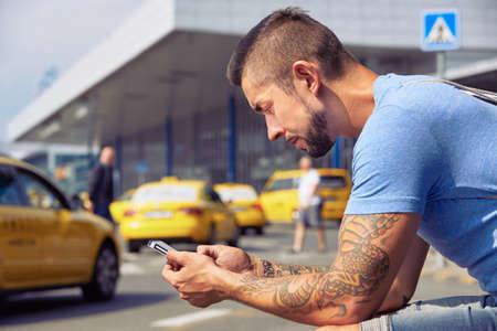 男は携帯電話アプリを使用してタクシーを順序付け 写真素材
