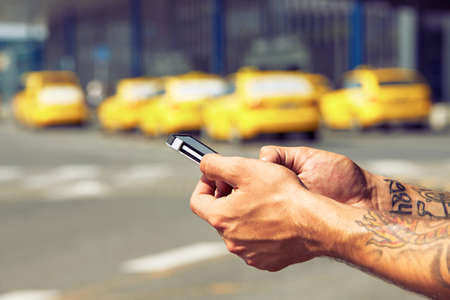 Hands of man ordering taxi, using mobile phone app