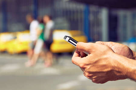 Hands of man ordering taxi, using mobile phone app Stock Photo