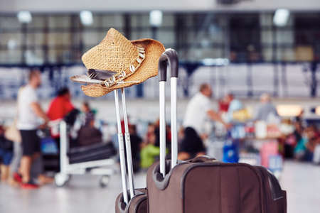 Luggage with straw hat at the airport terminal Stockfoto