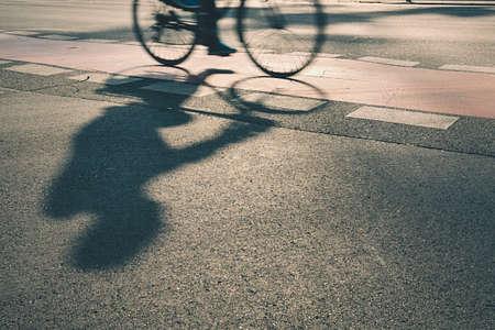Sziluettje kerékpáros az utcán napkeltekor