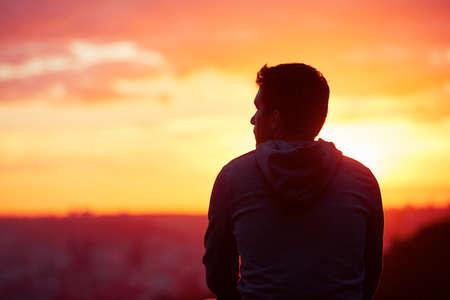 soledad: Hombre joven está mirando la salida del sol.