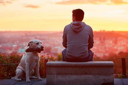 Junger Mann mit seinem Hund am Sonnenaufgang.